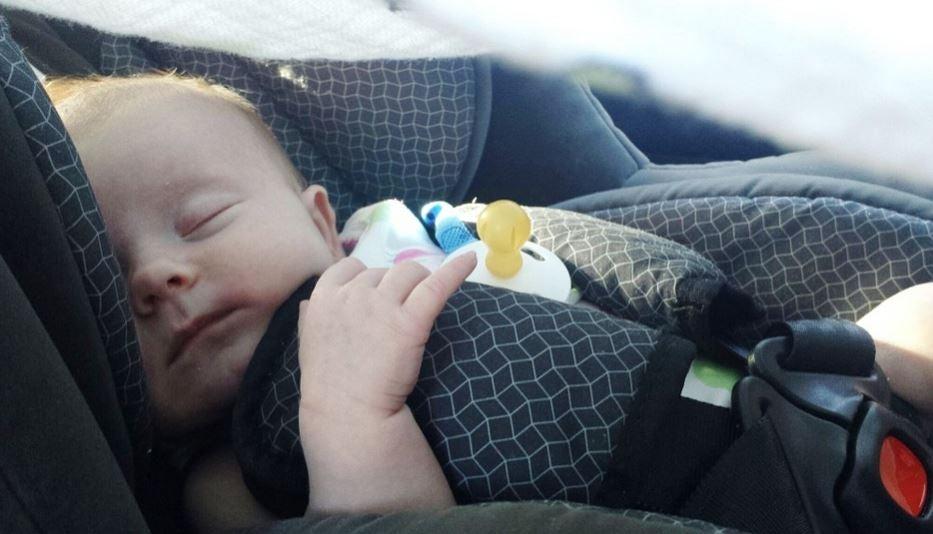 Bebe dormido en el coche con la silla de seguridad.