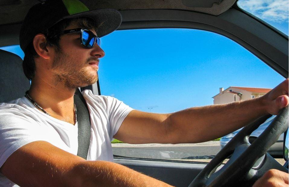 Chico joven conduciendo con gafas de sol.