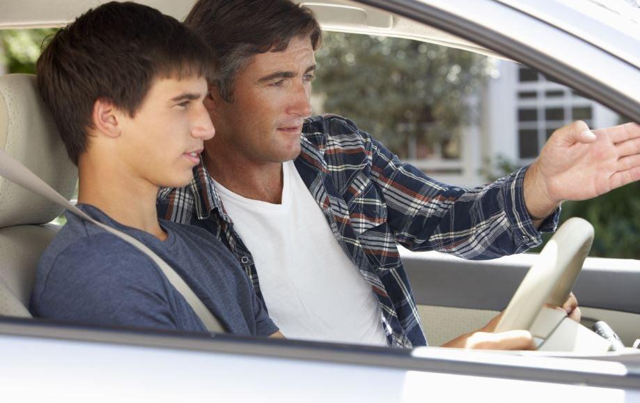 Un padre enseñando a su hijo a conducir.